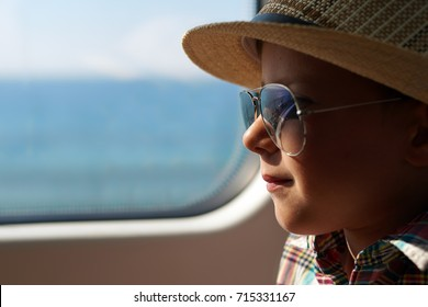 Cute boy in sunglasses and sunhat travelling by train.
