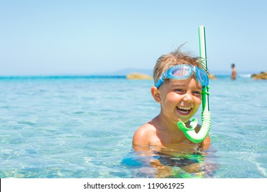 Cute boy in swimming goggles and snorkel swimming in the transparent sea