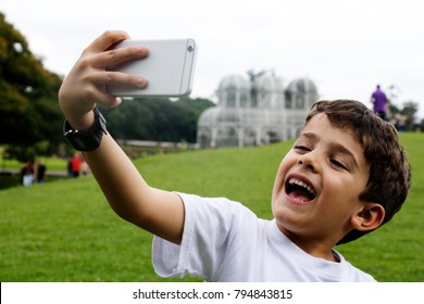 Cute boy taking a selfie with a mobile phone.