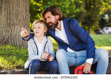 Cute boy talking with dad on a walk after school. Bearded man and his son outside. Happy father and son spending time together. Back to school concept. Family, relationship and lifestyle concept.