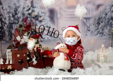 Cute boy, toddler child, having his christmas pictures taken playing in the snow outdoors, wearing protective mask, Christmas 2020 concept studio shot
