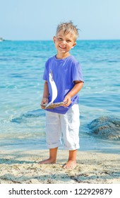 Cute boy with toy ship in hands ashore. Vertical view