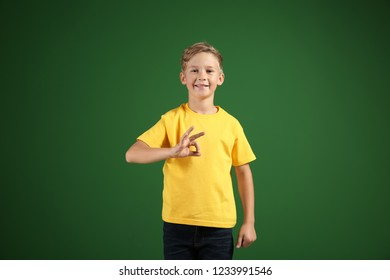 Cute boy in t-shirt showing OK gesture on color background