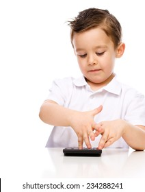 Cute boy is using calculator, isolated over white
