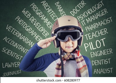 Cute boy wearing an aviator helmet and showing a saluting gesture with his dreams on the chalkboard
