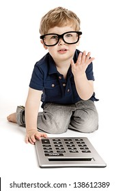 Cute boy wearing bit glasses doing maths with fingers and calculator.
