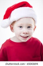 Cute boy wearing a santa claus hat studio portrait