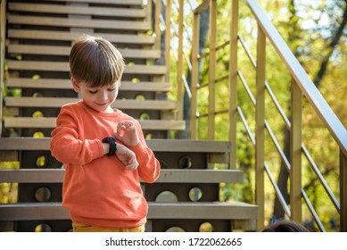 A cute boy wearing stylish shirt stay near school, looking at his smart watch touching the screen. A child using electronic device. Lifestyle concept.