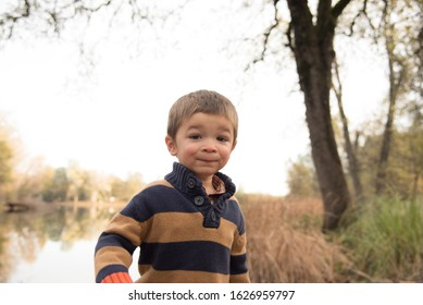 Cute boy wearing sweater with lake in background
