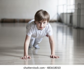 Cute boy in white clothes practicing capoeira (brazilian martial art that combines elements of dance, acrobatics and music)  in gym