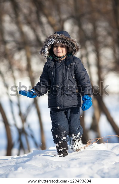 Cute boy in a winter jacket, playing with snow