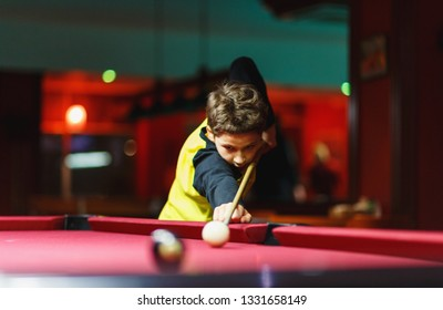 Cute boy in yellow t shirt plays billiard or pool in club. Young Kid learns to play snooker. Boy with billiard cue strikes the ball on table. Active Leisure, sport, hobby concept