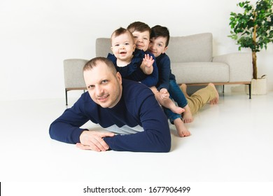 The Cute boys and baby with father looking at camera and smiling while at home