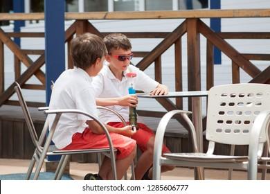 Cute boys drinks refreshing drink in summer in cafe. colorful granita