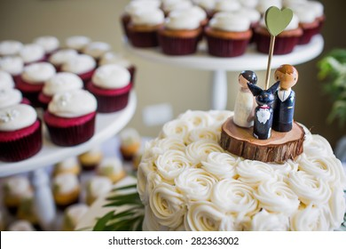 Cute bride, groom, and dog wedding cake topper with cupcakes in the background