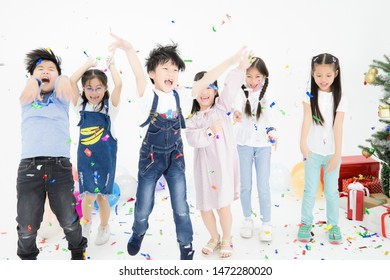 The cute and bright Asian children are jumping with smiling faces and enjoying the Christmas party.