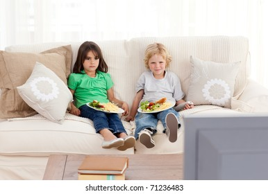 Cute brother and sister having dinner on the sofa in front of the television