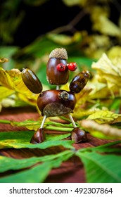 cute brown chestnut figure among yellow green autumn leaves