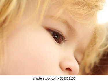 Cute brown eyes on adorable face of baby boy with cheeks and blond hair outdoors on sunny summer day on blurred background