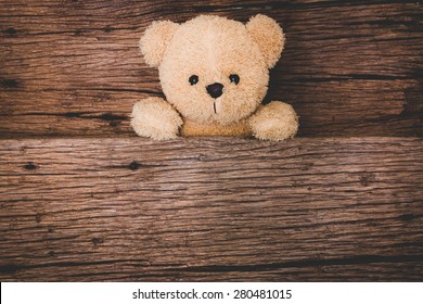 Cute brown teddy bear in old wood background