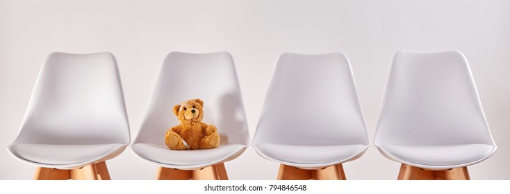 Cute brown teddy bear on a seat in the waiting room with empty chairs of a hospital or a health center for children