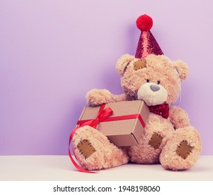 cute brown teddy bear in a red cap sits and holds a brown box with a gift, festive background, copy space