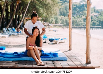 Cute brunette doing massage on the beach tanned woman
