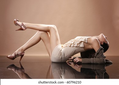Cute brunette in earthy outfit on mirrored floor