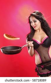 Cute brunette flipping pancakes in lingerie
