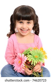 Cute brunette four year old girl smiling and holding colorful daisies on a white background