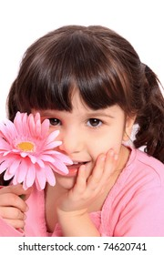 Cute brunette four year old girl being shy, hiding behind a colorful pink daisy on a white background