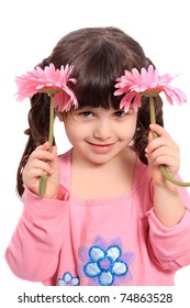 Cute brunette four year old girl being shy, hiding behind  colorful pink daisies on a white background