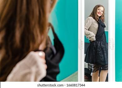 Cute brunette girl choosing her outfit, looking herself in the mirror.