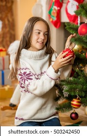 Cute brunette girl decorating Christmas tree at living room