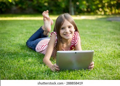 Cute brunette girl relaxing on grass park and holding digital tablet