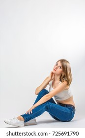 cute brunette girl sits on a white background in studio