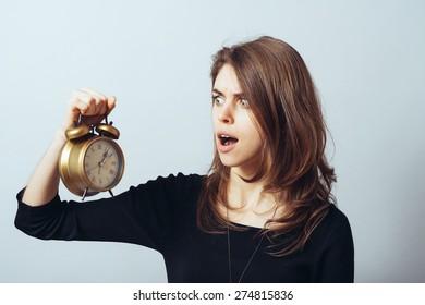 cute brunette girl slept with horror looks at an alarm clock