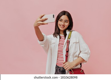 Cute brunette lady in striped t-shirt and eyeglasses holds red handbag. Pretty woman in white shirt takes selfie on pink background.