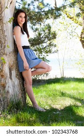 Cute brunette leaning against a tree