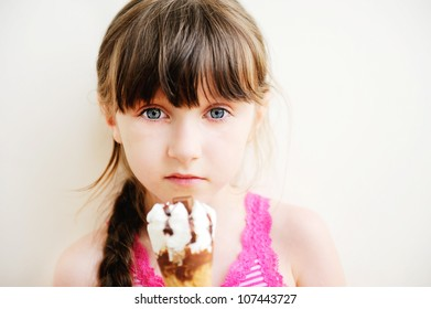 Cute brunette little girl with ice cream on white background