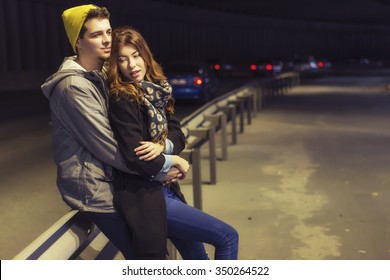 Cute brunette loving couple on a date. cold autumn, winter or spring night, european city. copy space