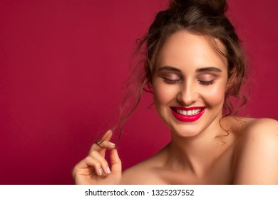 Cute brunette model with flawless skin and creative colorful make up on dark pink background. She wears a funny bun as a hairstyle and have solid pink lips make up