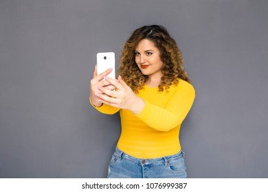 Cute brunette plus size woman with curly hair in yellow sweater and jeans standing on a neutral grey background. She makes selfie, photographing herself on her mobile phone. Copy space
