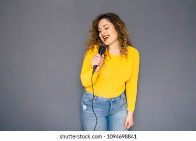 Cute brunette plus size woman with curly hair in yellow sweater and jeans standing on a neutral grey background. She holding mocrophone with her hands, singing song and dancing happily
