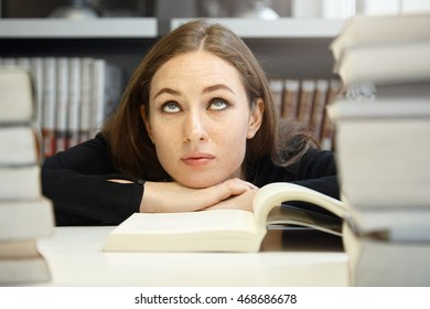 Cute brunette student girl in black jacket studying and reading textbook or manual in university library but having hard time understanding material, rolling her eyes, looking bored and confused