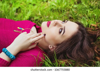Cute brunette woman in bright knitted pink sweater laying on the grass in the park. Dreaming woman on the grass.