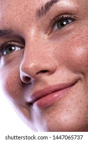 Cute brunette woman with freckles all over her face. Clean flawless fresh skin. Close up beauty concept of skincare and natural make up