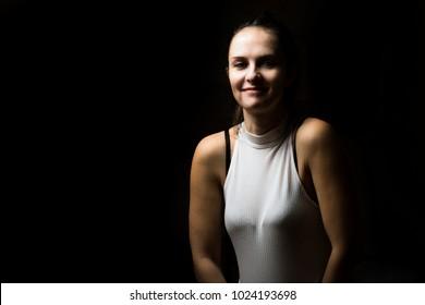 Cute brunette woman with long hair posing in low key