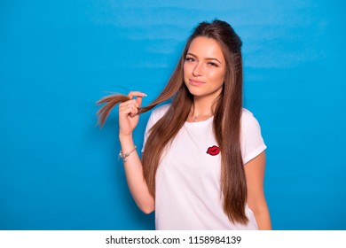 Cute brunette woman with long hair posing in white t-shirt on a blue background. Emotional portrait. She flirts