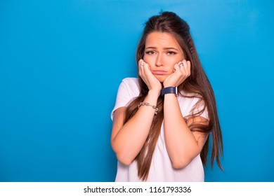 Cute brunette woman with long hair posing in white t-shirt on a blue background. Emotional portrait. She sad
